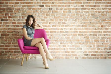 Mujer elegante en el sillón de color rosa Foto de archivo
