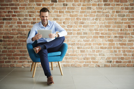 Digital tablet used by handsome man Stock Photo