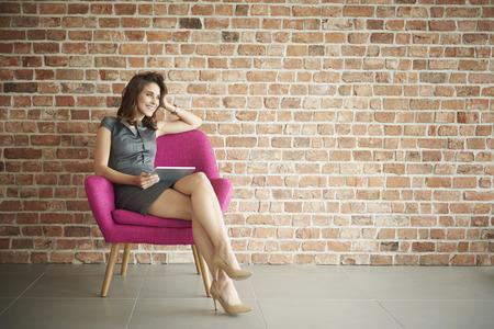 ピンクの肘掛け椅子に座って実業家