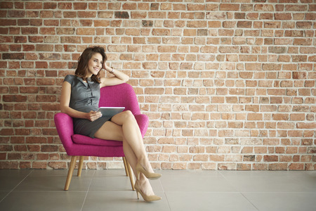Businesswoman sitting on the pink armchair