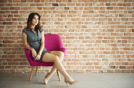 donna sognante sul muro di mattoni