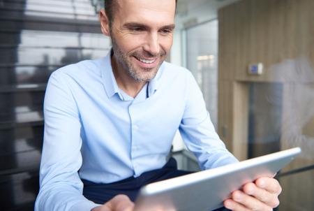 Hombre navegando tableta digital en escaleras