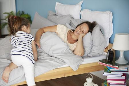 disturbing: Girl disturbing her tired mum