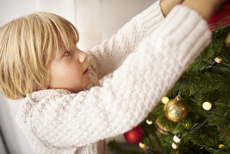 decorating christmas tree: Little boy decorating Christmas tree at home