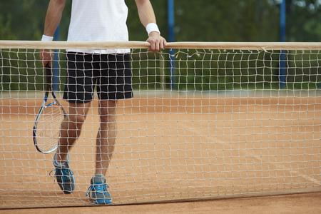 Man standing behind a tennis net