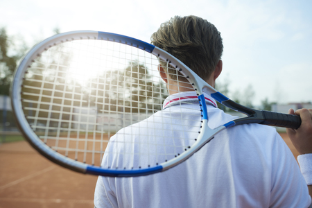 sports clothing: Man is holding a tennis racket