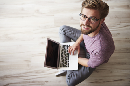 man with laptop: Man sitting on the floor and using the laptop Stock Photo