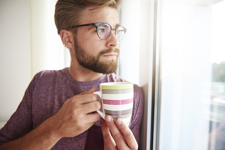 man looking out: Thoughtful man looking out the window with coffee