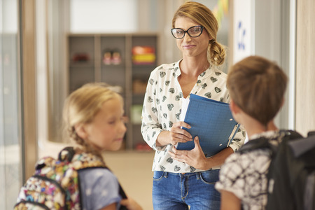 elementary school: Two pupils talking with a teacher Stock Photo