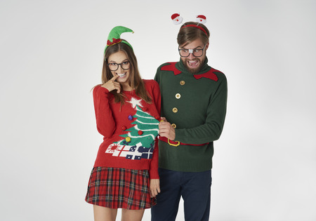 flirty: Flirty nerds in Christmas jumpers Stock Photo