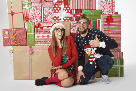 Wall of Christmas presents and cheerful couple Stock Photo