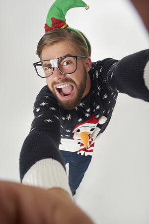 Man in Christmas clothes taking a selfie