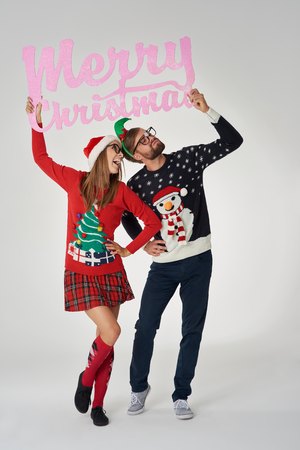 Young couple holding banner with Christmas greetings Stock Photo