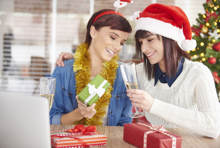 Woman is showing her Christmas present to friend Stock Photo