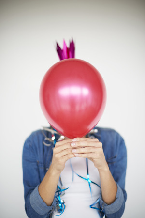 Woman hiding behind a red balloon