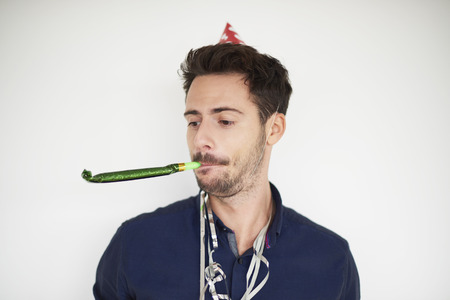 blower: Dark haired man with party horn blower