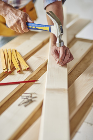 Carpenter with hammer hits wood Stock Photo