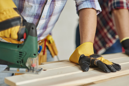 electric saw: Carpenter is sawing wooden planks by electric saw Stock Photo