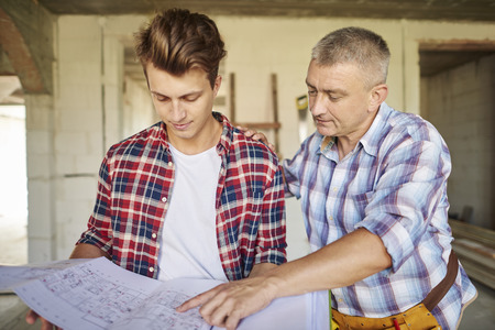resolving: Carpenters looking at project plan and thinking about next move Stock Photo