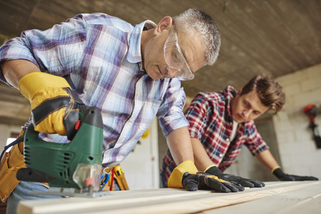 Creative carpenter works with younger one Stock Photo