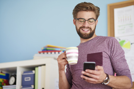 mobilephone: Man browsing mobilephone and drinking coffee Stock Photo