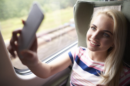persona viajando: Blonde woman taking selfie in the train