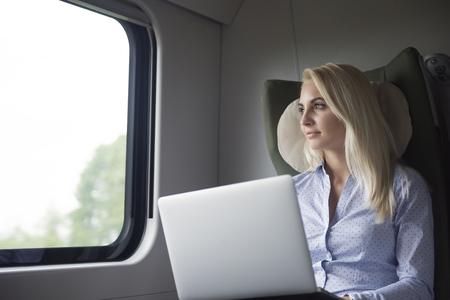 persona viajando: Mujer pensativa con la computadora portátil en el tren Foto de archivo