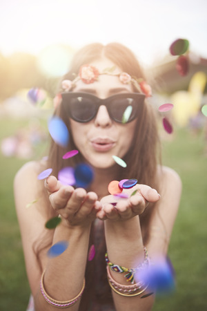 Colorful confetti blew by girl