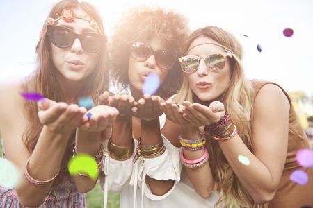 Les filles soufflant des morceaux de confettis Banque d'images