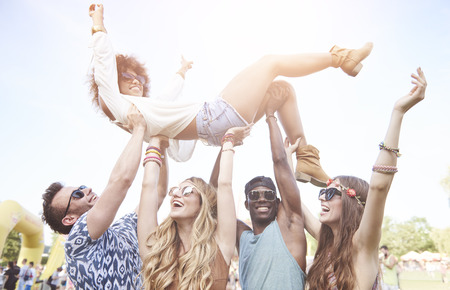 Excited woman crowd surfing at music festival