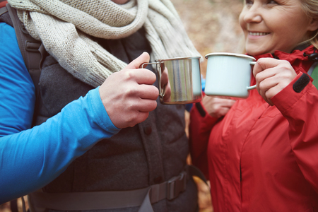 lower section view: Couple drinking hot tea from metal mugs