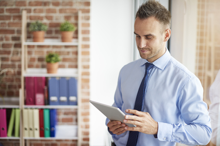 busy person: Browsing digital tablet in the office