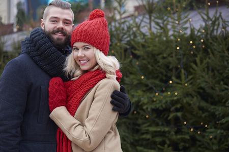pareja abrazada: Couple embracing next to christmas tree Foto de archivo