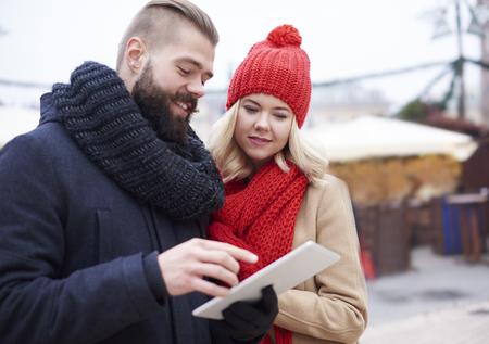 couples hug: Couple browsing digital tablet in winter