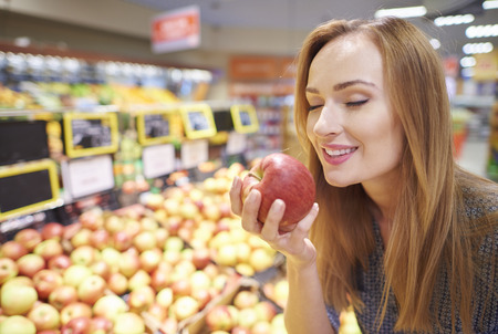 expanse: Woman choosing apples from grocery store Stock Photo