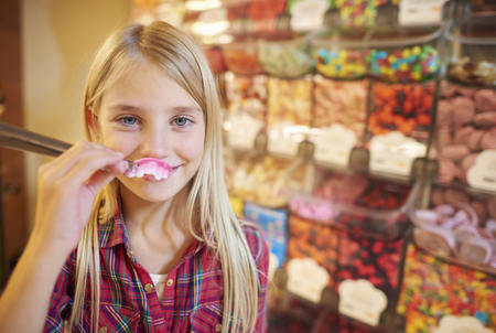shopping binge: Girl covering her lips by chewy candy