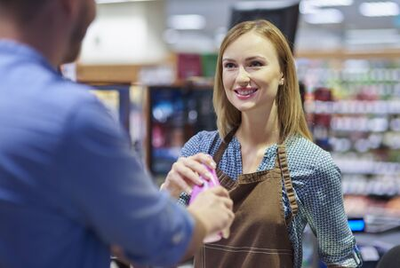 checkout: Woman working in gorcery checkout Stock Photo