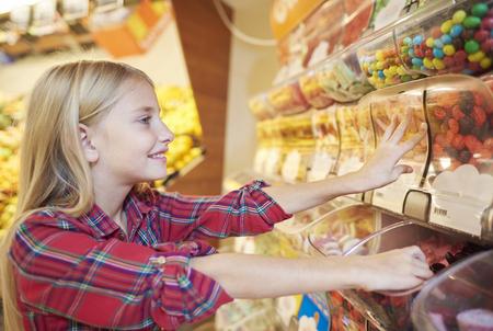sweetmeats: Side view of pretty girl reaching sweetmeats