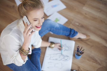 expertise: Woman drawing sketches and talking by the phone Stock Photo