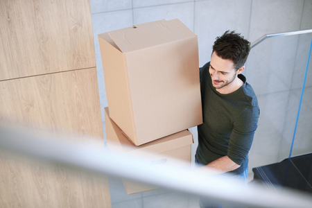 moving box: Man smiling and carrying moving box indoors