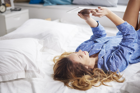 lying in bed: Woman lying on the bed with digital tablet Stock Photo