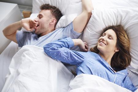 levantandose: Pareja de estiramiento y bostezo en la cama