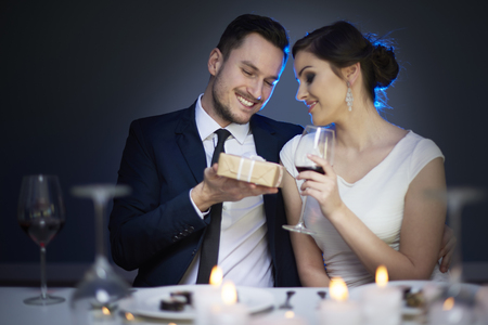 dinner wear: Young couple with present and glass of red wine  Stock Photo