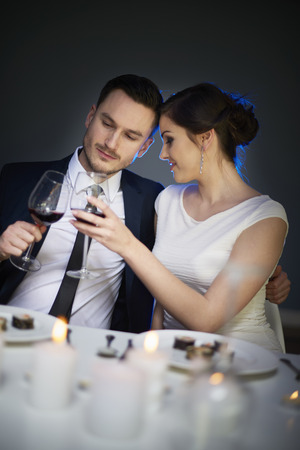 dinner wear: Couple toasting with wine during dinner time