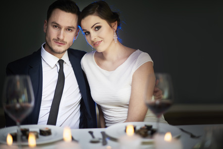 dinner wear: Couple sharing romantic moments at dinner