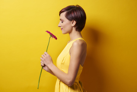 Young woman against yellow wall Stock Photo - 70174281