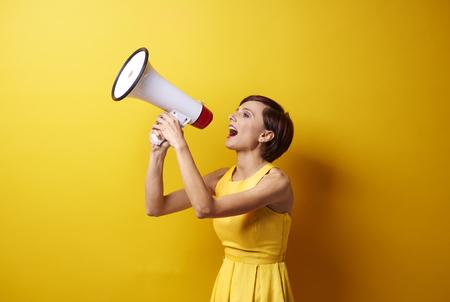 Vrouwelijk model met behulp van megafoon in fotosessie