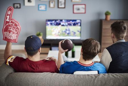 Drie mannen met Amerikaans voetbalmateriaal