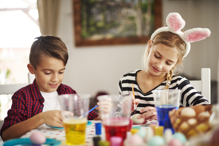 Elementary age kids painting eggs