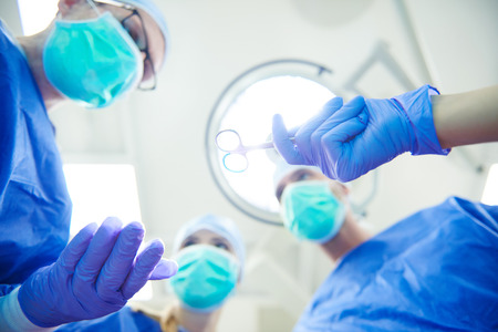 by pass surgery: Focus doctors passing medical scissors